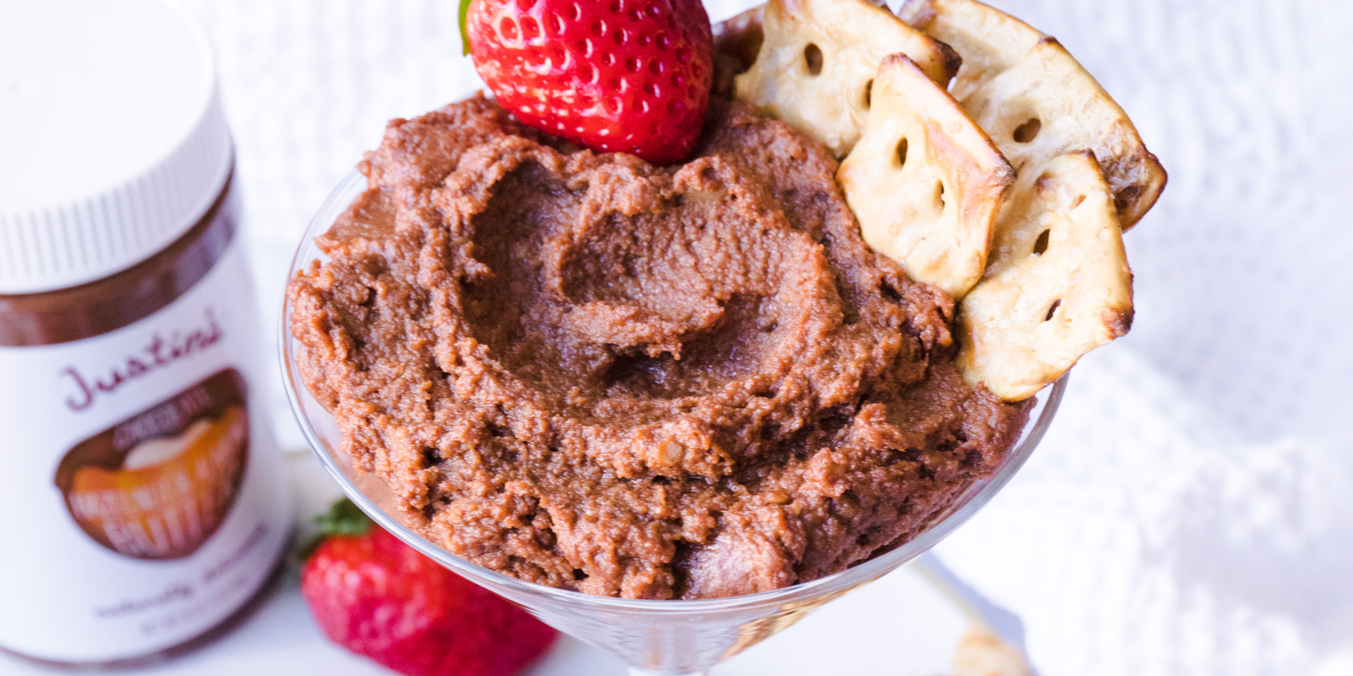 Chocolate Hazelnut and Almond Dessert Hummus on a clear glass with strawberries in the background