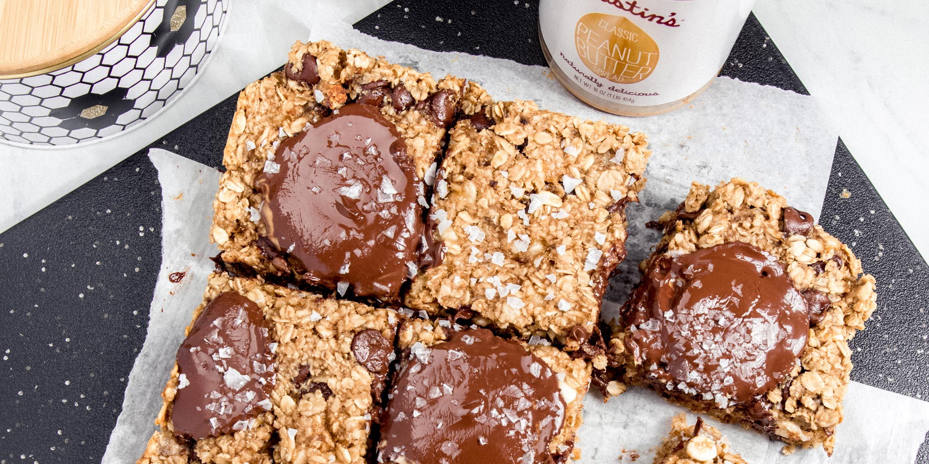 Chocolate Peanut Butter and Banana Oatmeal Cookie Bars on parchment papers on a black rectangular tray on a white background