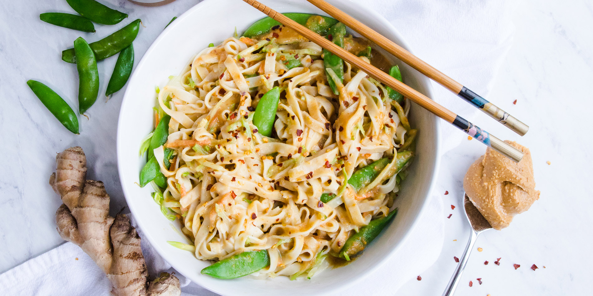 Easy Peanut-Ginger Noodles in a round white bowl with wooden chopsticks with fresh ginger in the background