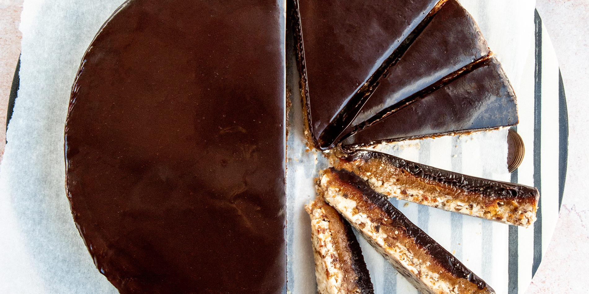 Almond Caramel Tart sliced and rotated for display over parchment, on a striped tabletop