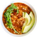 Icon of Chipotle Chicken Enchilada Soup in a white bowl with avocado and cilantro and tortillas on a checkered cloth