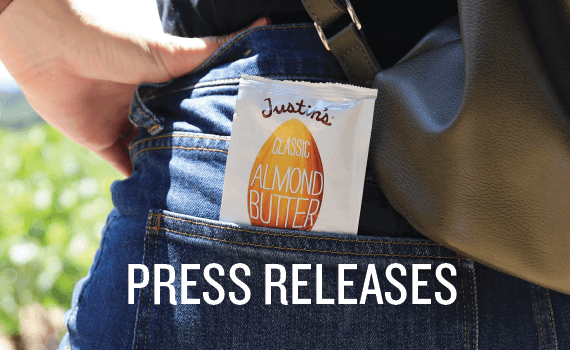 "Justin's Classic Almond Butter Spread Squeeze Pack in the back pocket of jeans with ""Press Releases"" in white font"