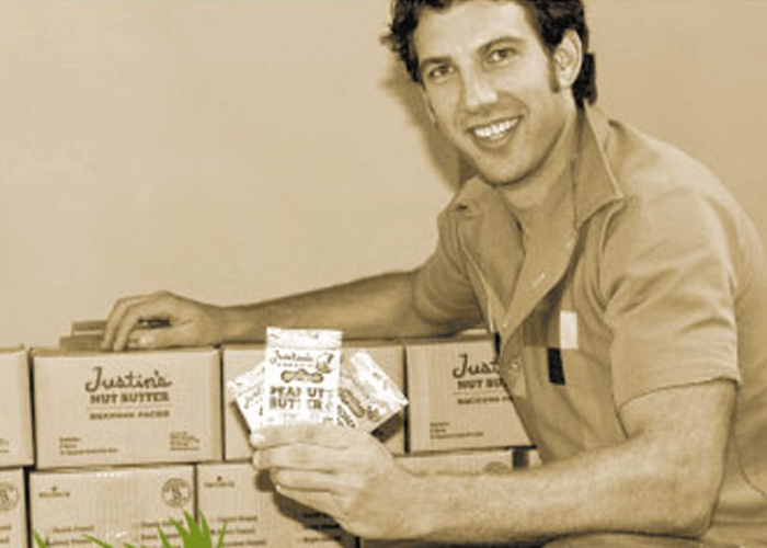 Sepia-toned photo of Justin holding packets of Justin's peanut butter spread squeeze pack with its initial package design