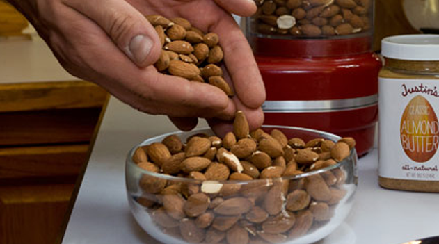 Hand pouring almonds into a round clear bowl
