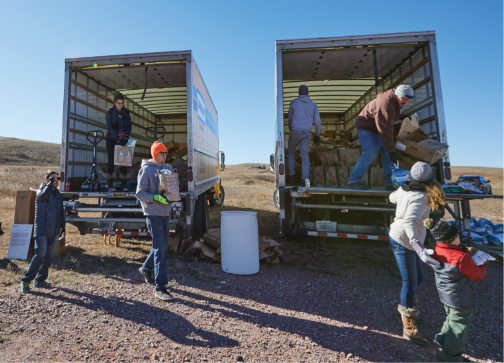 Workers moving parcels out of two big trucks on a sunny day in the middle of a grass field