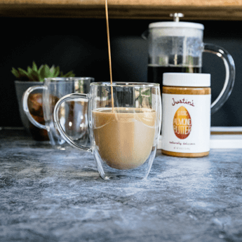 Almond Butter Bulletproof Coffee dripped down from a metal jug to a transparent cup on a grey marble tabletop and black wall