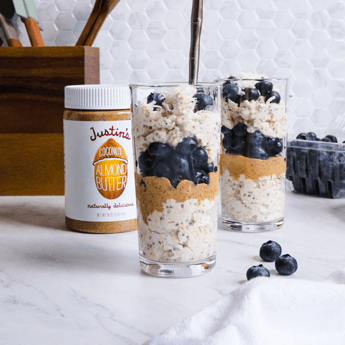Coconut Almond Butter Overnight Oats in a clear cup with a bamboo straw, and wooden baking utensils in the white background