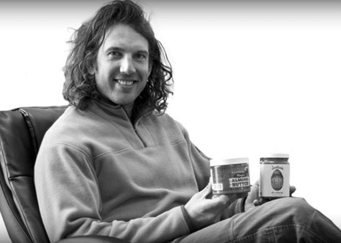 Black and white photo of Justin sitting in a chair and holding nut butter jars