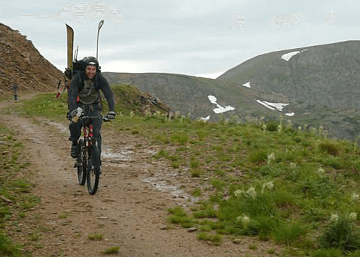 Outdoor shot of Justin with a backpack, riding a bike on a mountain trail