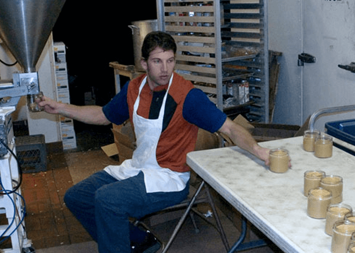 Justin sitting on chair, producing Justin's peanut butter products
