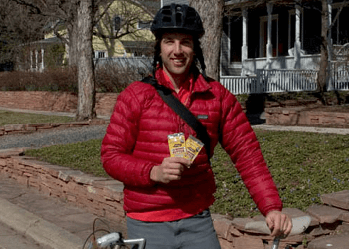 Outdoor shot of Justin wearing a bicycle helmet, holding products in hand while standing beside his bike