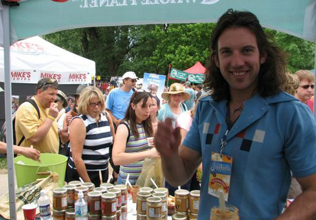 Justin standing under a festival stall with many people in the background