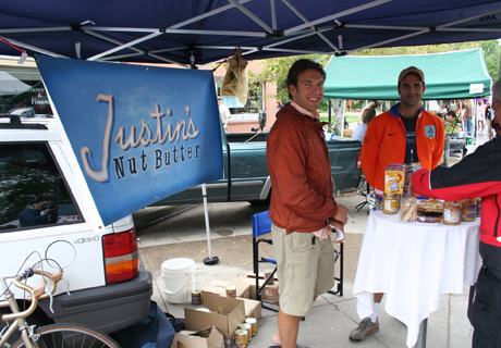 Justin under the stall at farmers market with a table display of his products