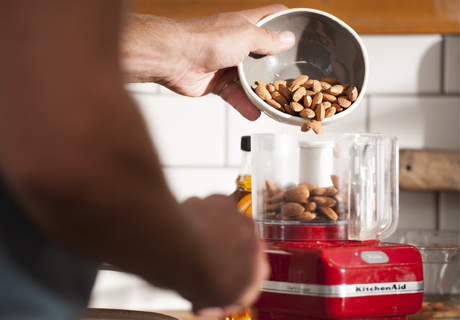 Hand pouring almonds from a bowl into a red Kitchen Aid mixer