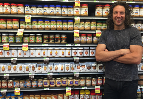 Smiling Justin with arms crossed in front of a shelf full of his products at a grocery store