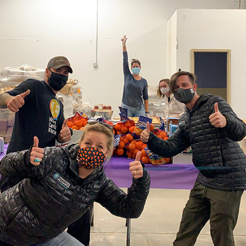 Team of people with masks on with their thumbs up, in front of a table with clementine bundles