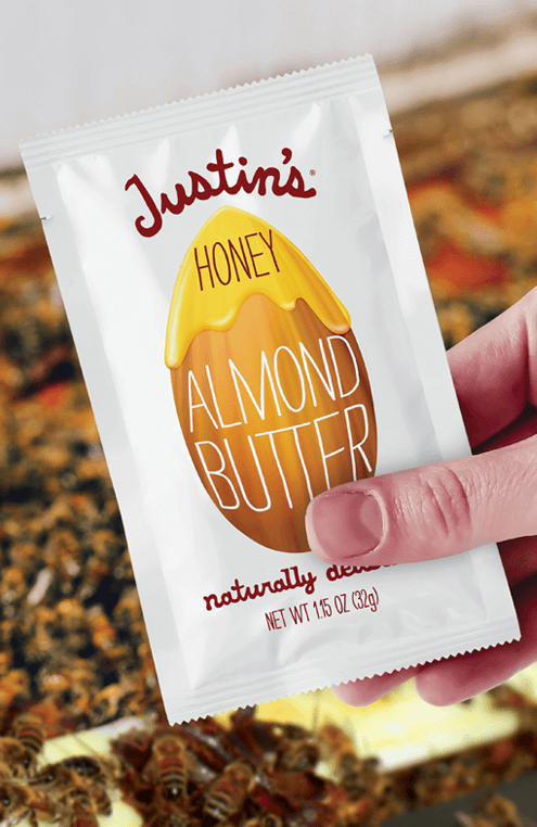 Hand holding Justin's Honey Almond Butter Spread Squeeze Pack 1.15 oz