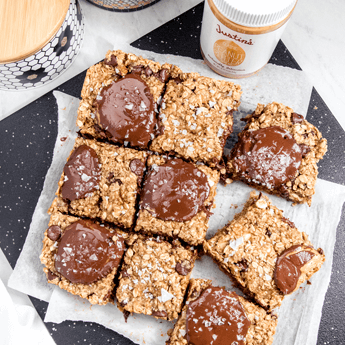 Chocolate Peanut Butter and Banana Oatmeal Cookie Bars on parchment papers on a black rectangular tray thumbnail image.