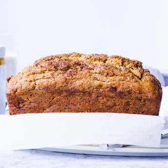 Cinnamon Almond Swirl Banana Bread on a white plate with silver cutlery on a white background (thumbnail image)