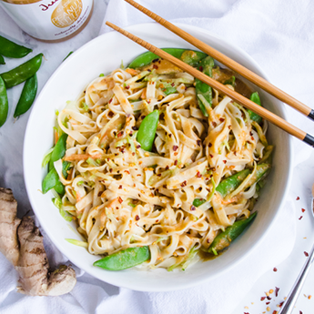 Easy Peanut-Ginger Noodles in a round white bowl with wooden chopsticks with fresh ginger in the background (thumbnail image)