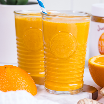 Orange Creamsicle Smoothie in tall glass cups with a white and blue straw with oranges in the background (thumbnail image)
