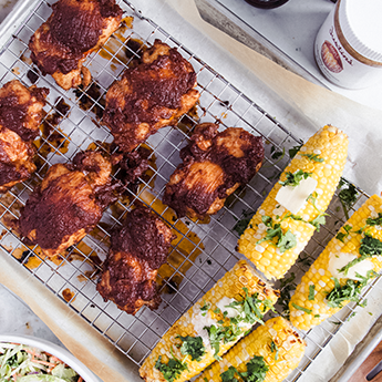 Maple Almond Barbecue Chicken beside some corn on the cob on a cooling rack in a tray with parchment paper
