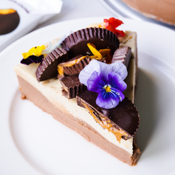 Peanut Butter Chocolate Cashew Cheesecake slice on a round, white plate (thumbnail image)