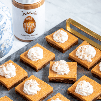Raw Maple Almond Pumpkin Pie Bars picked up by a golden spatula from a dark gray, rectangular stone plate thumbnail image.