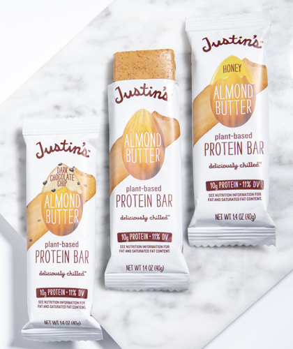 Justin's Almond Butter Protein Bars (Honey, Classic, Dark Chocolate) lined up on the right side of a marble background
