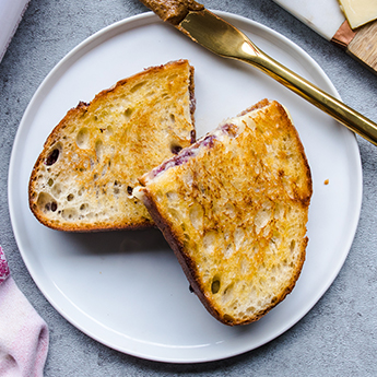 Almond Butter Blueberry Cheddar Melt on a ceramic plate with a gold butter knife (thumbnail)