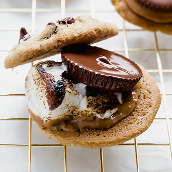 Chocolate Peanut Butter Cup Cookie S'mores laid out on gold cooking rack, atop white countertop