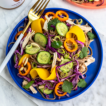 Summer Soba Salad on blue plate with a gold and white fork set on a marble countertop