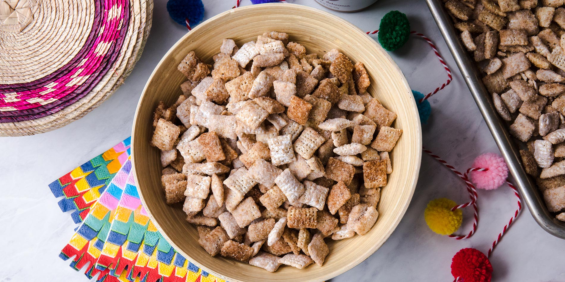 Bowl filled with Almond Butter Churro Puppy Chow atop marble countertop with decorative paper underneath