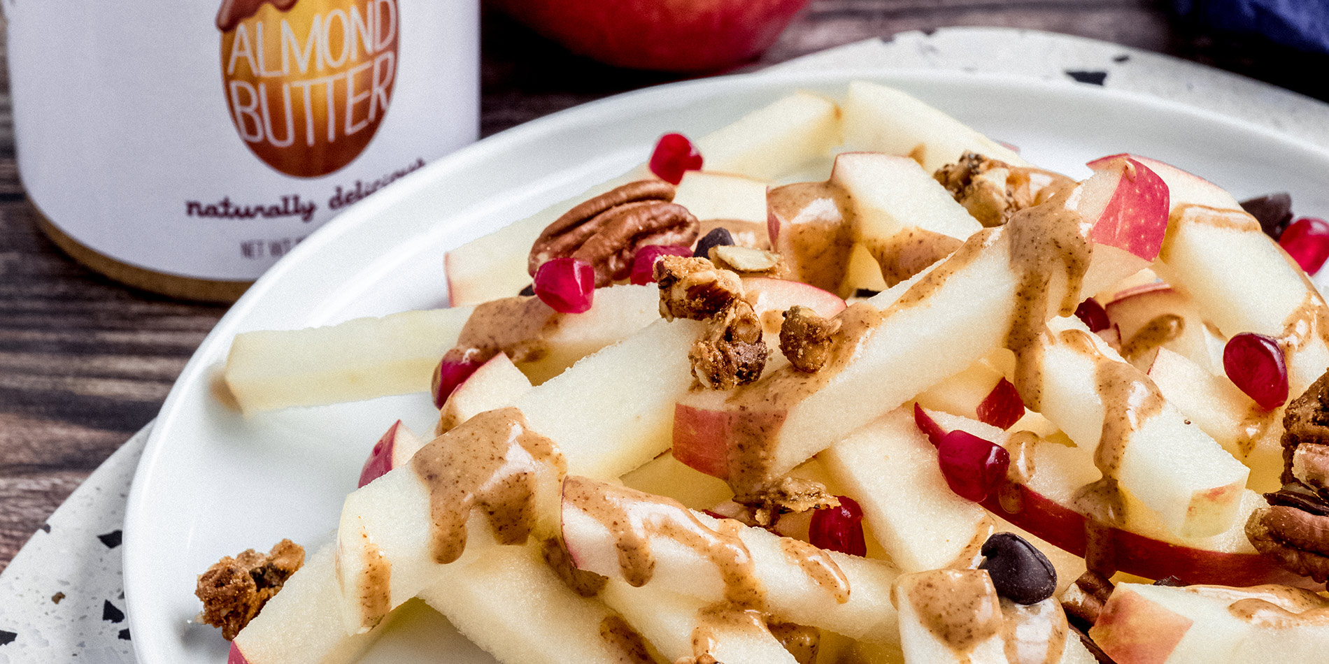 Apple Fries stacked on a ceramic plate, covered in Loaded dressing and toppings, on a dark wooden tabletop