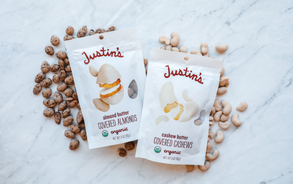 Justin's Almond Butter Covered Almonds and Cashew Butter Covered Cashews with its contents spread out behind each pouch