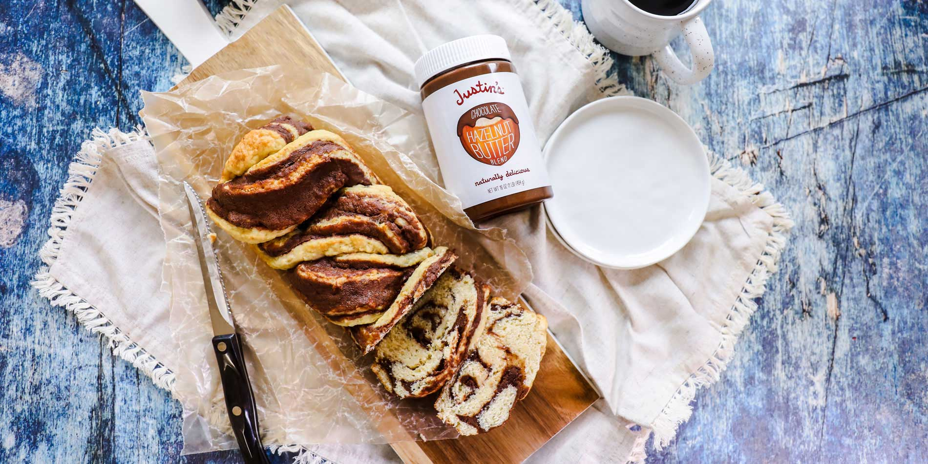 Chocolate Hazelnut Babka on a wooden serving board on a cloth beside a cup of coffee on a blue wood background