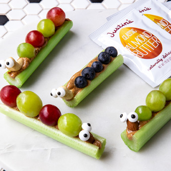 Celery sticks with peanut butter, grapes and blueberries on top.